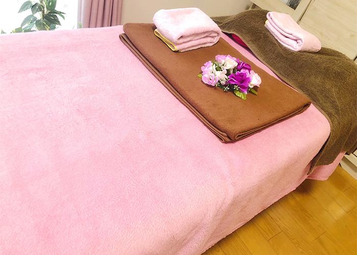 ピンクの布が掛けられた施術台アップ