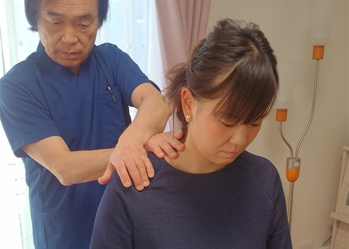 男性に右肩を施術される女性