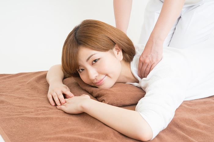 肩の施術を受けながらこちらをみる女性