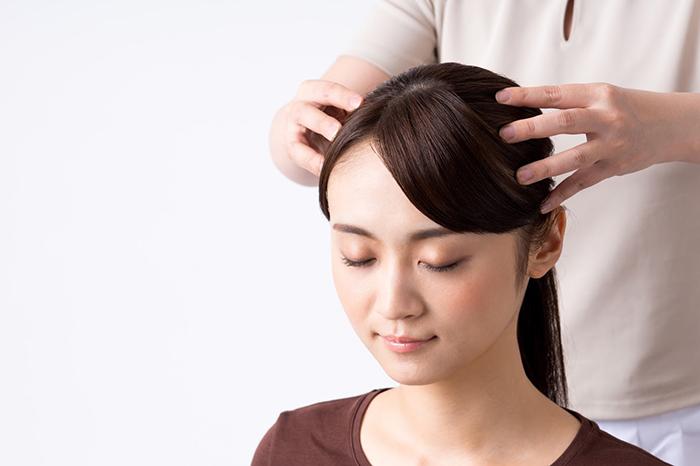 頭部の施術を受ける女性