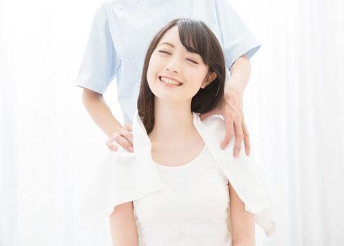 白い服を着た女性が肩を揉まれる正面